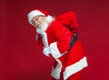 Χριστούγεννα Καλός και κουρασμένος Άγιος Βασίλης στα άσπρα γάντια φέρνει μια κόκκινη τσάντα με τα δώρα πέρα από τον ώμο του Απομο στοκ εικόνες