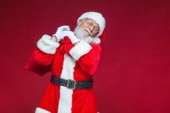 Χριστούγεννα Καλός και κουρασμένος Άγιος Βασίλης στα άσπρα γάντια φέρνει μια κόκκινη τσάντα με τα δώρα πέρα από τον ώμο του Απομο στοκ φωτογραφία