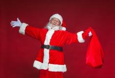 Χριστούγεννα Καλός χαμογελώντας Άγιος Βασίλης διέδωσε τα χέρια του στις πλευρές Σε ένα χέρι κρατά μια κόκκινη τσάντα με τα δώρα στοκ εικόνα