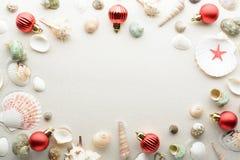 Χριστούγεννα καρτών εορτ&a Σφαίρες και θαλασσινά κοχύλια στην άμμο με το διάστημα αντιγράφων Στοκ Φωτογραφίες