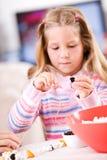 Χριστούγεννα: Κορίτσι που περνά κλωστή στα φρούτα επάνω Popcorn στη διακόσμηση γιρλαντών Στοκ φωτογραφία με δικαίωμα ελεύθερης χρήσης