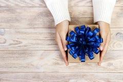 Χριστούγεννα λαβής χεριών γυναίκας ή νέο διακοσμημένο έτος κιβώτιο δώρων κιβώτιο δώρων με ένα μεγάλο μπλε τόξο Στοκ εικόνες με δικαίωμα ελεύθερης χρήσης