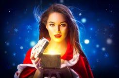 Χριστούγεννα Νέα γυναίκα brunette ομορφιάς στο κιβώτιο δώρων ανοίγματος κοστουμιών κομμάτων πέρα από το υπόβαθρο νύχτας διακοπών Στοκ Εικόνες