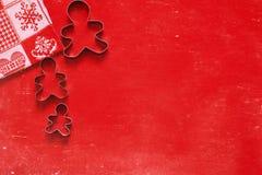 Χριστούγεννα, νέο υπόβαθρο διακοπών έτους, σύσταση, ταπετσαρία Κόπτες μπισκότων στο κόκκινο υπόβαθρο στοκ εικόνες