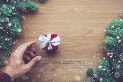 Χριστούγεννα, οι νέες έννοιες εορτασμού έτους με το ανθρώπινο κιβώτιο δώρων εκμετάλλευσης χεριών παρουσιάζουν/διακόσμηση με τον κ Στοκ Εικόνες