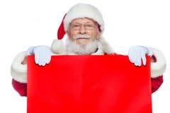 Χριστούγεννα Ο καλός Άγιος Βασίλης στα άσπρα γάντια κρατά ένα κενό χαρτόνι του κόκκινου χρώματος Θέση για τη διαφήμιση, για το κε στοκ φωτογραφία με δικαίωμα ελεύθερης χρήσης