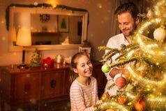 Χριστούγεννα - ο πατέρας και η κόρη διακοσμούν το χριστουγεννιάτικο δέντρο Στοκ Εικόνα