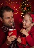Χριστούγεννα - ο πατέρας και η κόρη πίνουν το κακάο και κατοχή της διασκέδασης στοκ εικόνες