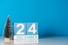 Χριστούγεννα παραμονής 24 Δεκεμβρίου Ημέρα 24 του μήνα Δεκεμβρίου, ημερολόγιο με λίγο χριστουγεννιάτικο δέντρο στο μπλε υπόβαθρο  Στοκ φωτογραφίες με δικαίωμα ελεύθερης χρήσης