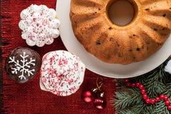 Χριστούγεννα που διακοσμούνται cupcakes και κέικ στο κόκκινο burlap υπόβαθρο τ Στοκ φωτογραφία με δικαίωμα ελεύθερης χρήσης