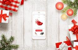 Χριστούγεννα που ψωνίζουν με το έξυπνο τηλέφωνο Αγοράζοντας τα παπούτσια on-line στον ιστοχώρο εμπορίου ή app Στοκ Εικόνες