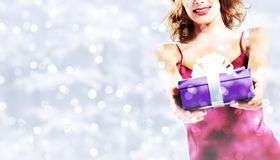 Χριστούγεννα που ψωνίζουν, χαμογελώντας γυναίκα με τη συσκευασία δώρων στο θολωμένο β Στοκ Εικόνες