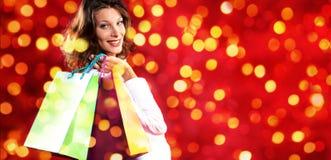 Χριστούγεννα που ψωνίζουν, χαμογελώντας γυναίκα με τις τσάντες στο θολωμένο φωτεινό λι Στοκ Εικόνα