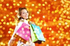 Χριστούγεννα που ψωνίζουν, χαμογελώντας γυναίκα με τις τσάντες στο θολωμένο φωτεινό λι Στοκ Φωτογραφίες