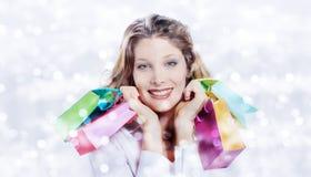 Χριστούγεννα που ψωνίζουν, χαμογελώντας γυναίκα με τις τσάντες στο θολωμένο φωτεινό λι Στοκ Φωτογραφία