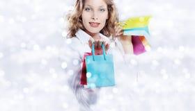 Χριστούγεννα που ψωνίζουν, χαμογελώντας γυναίκα με τις τσάντες στο θολωμένο φωτεινό λι Στοκ Εικόνες