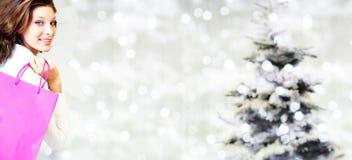 Χριστούγεννα που ψωνίζουν, χαμογελώντας γυναίκα με τις τσάντες στο θολωμένο φωτεινό λι Στοκ φωτογραφία με δικαίωμα ελεύθερης χρήσης