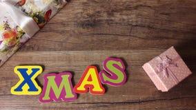 Χριστούγεννα σε έναν ξύλινο πίνακα με τα δώρα, κίνηση στάσεων, τοπ πυροβολισμός άποψης φιλμ μικρού μήκους
