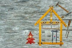 Χριστούγεννα σε ένα πρόσφατα χτισμένο σπίτι Δώρο στη Παραμονή Χριστουγέννων Υποθήκη για να χτίσει ένα σπίτι ανασκόπησης μπλε κτηρ Στοκ Φωτογραφία