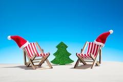 Χριστούγεννα στην παραλία: δύο καρέκλες με τα καπέλα Santa και το έλατο παιχνιδιών Στοκ φωτογραφία με δικαίωμα ελεύθερης χρήσης