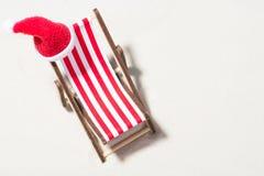 Χριστούγεννα στην παραλία: μια καρέκλα σαλονιών με ένα καπέλο Santa Στοκ φωτογραφία με δικαίωμα ελεύθερης χρήσης