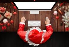 Χριστούγεννα στο σπίτι Άγιου Βασίλη Χρήση Άγιου Βασίλη ένας υπολογιστής για να απαντήσει στις επιστολές στοκ φωτογραφίες με δικαίωμα ελεύθερης χρήσης