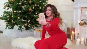 Χριστούγεννα, το όμορφο κορίτσι στο φόρεμα διακοπών στις τηλεοπτικές κλήσεις λέει, επιθυμεί μια καλή χρονιά στο υπόβαθρο διακοσμη απόθεμα βίντεο