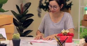 Χριστούγεννα τυλίγματος γυναικών ή άλλο χειροποίητο παρόν διακοπών στο έγγραφο απόθεμα βίντεο
