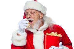 Χριστούγεννα Χαμογελώντας, καλός Άγιος Βασίλης στα άσπρα γάντια με το στόμα του ανοικτό κρατά έναν κόκκινο κάδο με popcorn με ένα στοκ εικόνα με δικαίωμα ελεύθερης χρήσης