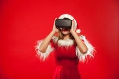 Χριστούγεννα, Χριστούγεννα, χειμώνας, έννοια ευτυχίας - όμορφο νέο brunette με μακρυμάλλη στη φθορά καπέλων αρωγών santa Στοκ Εικόνες
