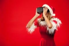 Χριστούγεννα, Χριστούγεννα, χειμώνας, έννοια ευτυχίας - όμορφο νέο brunette με μακρυμάλλη στη φθορά καπέλων αρωγών santa Στοκ Εικόνα