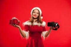 Χριστούγεννα, Χριστούγεννα, χειμώνας, έννοια ευτυχίας - όμορφο νέο brunette με μακρυμάλλη στη φθορά καπέλων αρωγών santa Στοκ Φωτογραφίες
