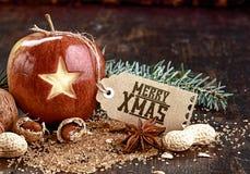 Χριστούγεννα Apple και καρύδια στον ξύλινο πίνακα Στοκ εικόνα με δικαίωμα ελεύθερης χρήσης