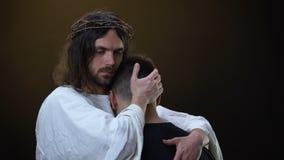 Χριστός που αγκαλιάζει το καταθλιπτικό parishioner που φαίνεται κεκλεισμένων των θυρών, ευγένεια Θεών, προστασία απόθεμα βίντεο