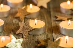 Χρονικά κεριά Χριστουγέννων με τις χρυσές διακοσμήσεις μορφής αστεριών στοκ φωτογραφία με δικαίωμα ελεύθερης χρήσης