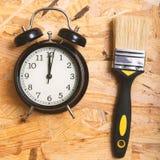 Χρονική έννοια DIY Εργαλεία που περιβάλλουν ένα μαύρο ξυπνητήρι στοκ εικόνα