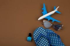 Χρονικό αεροπλάνο περιπέτειας, πτώσεις κτυπήματος, γυαλιά ηλίου, στιλβωτική ουσία καρφιών στο καφετί υπόβαθρο Στοκ Φωτογραφίες