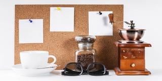 Χρονικό πρότυπο Coffe Χειρωνακτικός μύλος καφέ, ένα βάζο των φασολιών καφέ, ένα άσπρο φλυτζάνι, ένας υπολογιστής γραφείου με τις  στοκ φωτογραφίες
