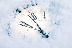 Χρονικό ρολόι Χριστουγέννων κάτω από το χιόνι Στοκ Εικόνες