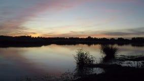 Χρονικό σφάλμα ενός κόκκινου ηλιοβασιλέματος πέρα από μια μικρή λίμνη στις Κάτω Χώρες φιλμ μικρού μήκους