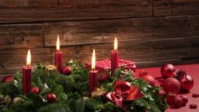Χρονικό σφάλμα τεσσάρων καίγοντας κόκκινων κεριών σε ένα στεφάνι εμφάνισης με την εορταστική διακόσμηση απόθεμα βίντεο