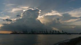 Χρονικό σφάλμα των δραματικών σύννεφων πέρα από το ναυπηγείο με τους γερανούς κατά μήκος των στενών της Σιγκαπούρης στο ηλιοβασίλ φιλμ μικρού μήκους