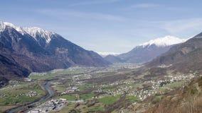 Χρονικό σφάλμα των ορών με το σύνολο βουνών του χιονιού, των σύννεφων και μιας πόλης με την πράσινη χλόη απόθεμα βίντεο
