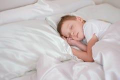 7χρονος ύπνος αγοριών στο κρεβάτι του Στοκ εικόνες με δικαίωμα ελεύθερης χρήσης