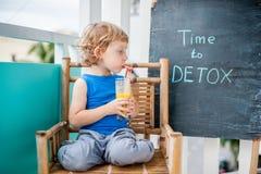ΧΡΟΝΟΣ στην επιγραφή κιμωλίας DETOX Το αγόρι πίνει φρέσκο, υγιής, detox ποτό που γίνεται από τα φρούτα Κούνημα φρούτων, φρέσκος χ Στοκ εικόνες με δικαίωμα ελεύθερης χρήσης