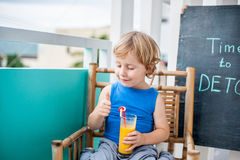 ΧΡΟΝΟΣ στην επιγραφή κιμωλίας DETOX Το αγόρι πίνει φρέσκο, υγιής, detox ποτό που γίνεται από τα φρούτα Κούνημα φρούτων, φρέσκος χ Στοκ φωτογραφία με δικαίωμα ελεύθερης χρήσης