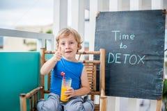 ΧΡΟΝΟΣ στην επιγραφή κιμωλίας DETOX Το αγόρι πίνει φρέσκο, υγιής, detox ποτό που γίνεται από τα φρούτα Κούνημα φρούτων, φρέσκος χ Στοκ Φωτογραφίες