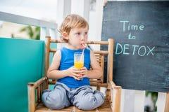 ΧΡΟΝΟΣ στην επιγραφή κιμωλίας DETOX Το αγόρι πίνει φρέσκο, υγιής, detox ποτό που γίνεται από τα φρούτα Κούνημα φρούτων, φρέσκος χ Στοκ Φωτογραφία