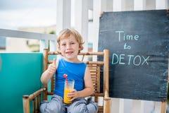 ΧΡΟΝΟΣ στην επιγραφή κιμωλίας DETOX Το αγόρι πίνει φρέσκο, υγιής, detox ποτό που γίνεται από τα φρούτα Κούνημα φρούτων, φρέσκος χ Στοκ φωτογραφίες με δικαίωμα ελεύθερης χρήσης