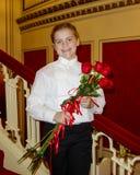 10χρονο κορίτσι που στέκεται στο κόκκινο κλιμακοστάσιο που κρατά τα κόκκινα τριαντάφυλλα Στοκ Εικόνα